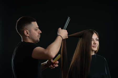 Close up of a hairdresser straightening the hair with a flat iron to client. Hairdressing session Standard-Bild