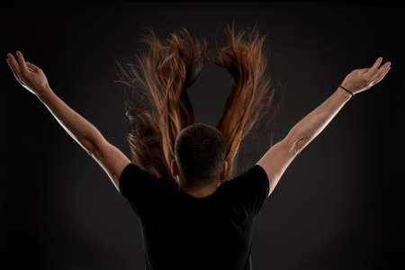 Young hairstylist in black t-shirt stands back to the camera with raised hand behinde young woman with long brunette fluttering hair