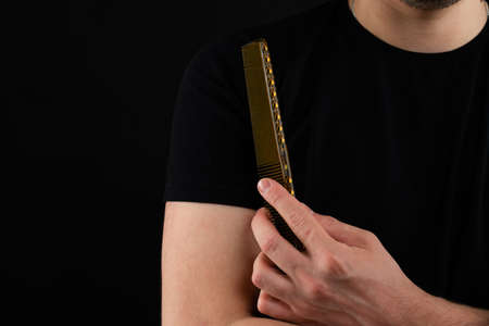 Cropped photo of a handsome barber in black t-shirt holding comb Standard-Bild