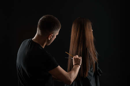 Beautiful young hairdresser doing hairstyle to female client in beauty salon Standard-Bild