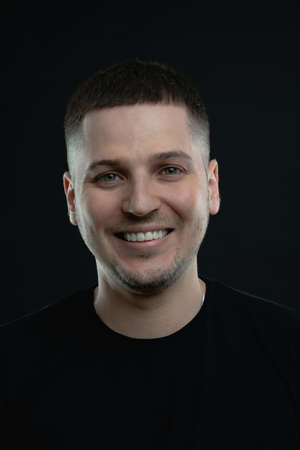 Close up portrait of young smiling handsome guy in black t-shirt isolated on black