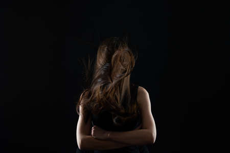 Woman with hair over her face, holds hands together Standard-Bild