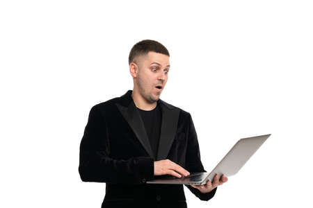Side profile view portrait of confident surprised shocked handsome cheerful man dressed in classic elegant suit using netbook for work