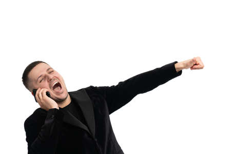 Positive confident happy young male manager in dark blue suit standing against isolated background and gesturing hand while communicating on mobile phone