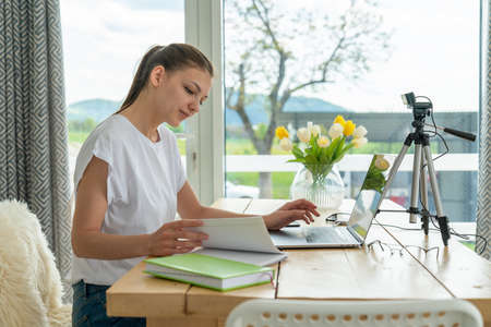 Focused young freelance woman sitting on the table at home with laptop, working remotely online from home Standard-Bild - 152094994