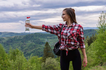 Girl trekking outdoors on the mountains, she is holding a water bottle and carrying a backpack with hiking pole Standard-Bild - 152095510