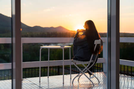 Young woman traveler holds cup of tea in her hands at mountain resort