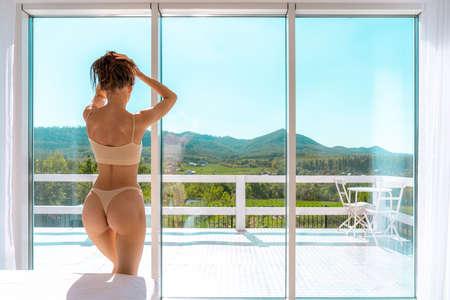 Young And Beautiful Brunette Woman Posing Near The Windowsill. Daylight From The Window