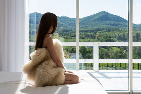 Attractive young woman wrapped in a fur coat sitting in hotel room. Portrait of sensual female daydreaming near a window