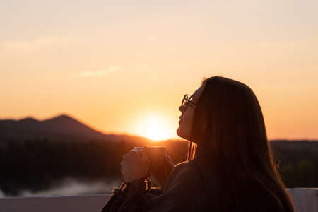 Girl with closed eyes drinking coffee contemplating views at sunset Standard-Bild - 152095078