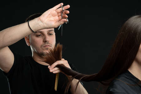 Modern professional man working as hairdresser and cutting hair tips of a female customer in beauty salon