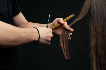 Male hairdresser with comb and scissors makes a haircut for a woman closeup