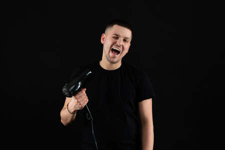 Funny young man 20s years old in black t-shirt hold blow dry hair isolated on black wall background, studio portrait