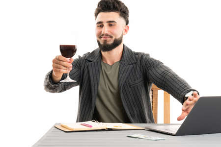 Young bearded man sitting by the table holding a glass of wine in his hand and cover the web cam 版權商用圖片
