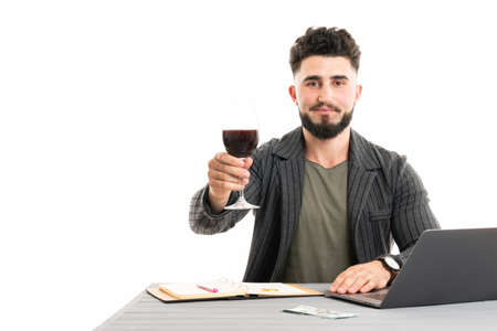 Businessman getting a glass of wine and using laptop Standard-Bild - 152631354
