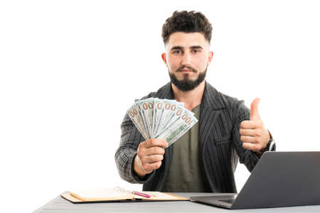 Portrait of an excited young businessman dressed in suit showing money banknotes and giving thumbs up isolated over white background 版權商用圖片