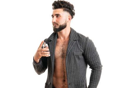 Businessman applying perfume on white background. Masculine perfume, bearded man in a suit 版權商用圖片