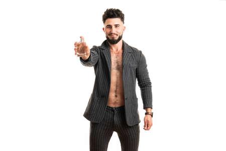 Man hold perfume bottle. Bearded man with deodorant isolated on white background 版權商用圖片