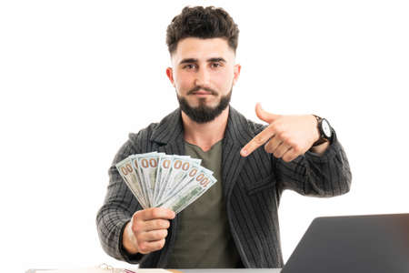Senior man holding dollar money very happy pointing with hand and finger to the side