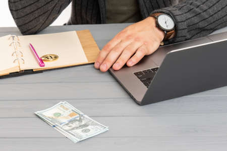 Close up man hand with watch near Bitcoin, laptop and us dollar bill