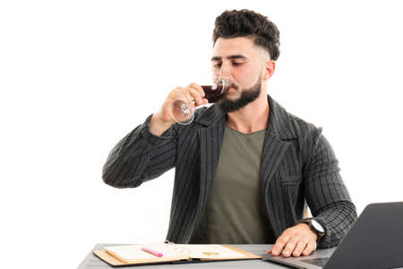 Handsome businessman dressed in the suit drinking red wine sitting