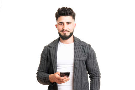 Positive European American male with smile, holds modern cell phone, types text message and feedback, surfes social networks, rejoices high speed interent connection