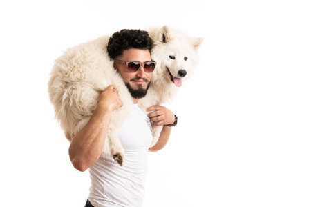 Stylish bearded man in glasses holds samoyed dog on his back, smiling and looking at the camera Standard-Bild - 152631374