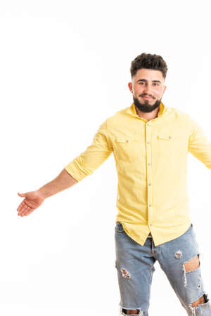 Portrait of guy wearing denim shirt, standing with wide hands while laughing, isolated over white background