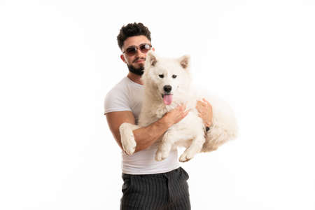 Pleased man in glasses holds samoyed dog in his hands