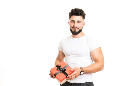 Handsome bearded overjoyed man wearing casual clothes holding present box standing isolated over white background 版權商用圖片