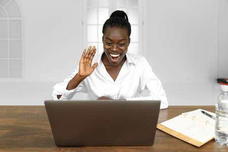 Corporate communication. Black businesswoman talking on web cam laptop in modern office. Free space 版權商用圖片