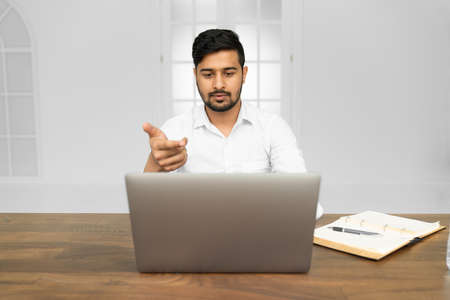 Young Asian Indian businessman working on laptop in modern office 版權商用圖片