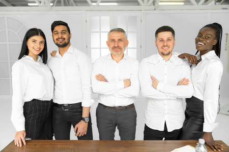 Group picture of happy diverse multiethnic young businesspeople in white shirts posing together at workplace in office