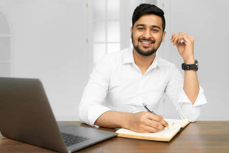 Asian student studying, learning language, online education concept. Portrait of handsome Indian businessman using laptop computer, working in office