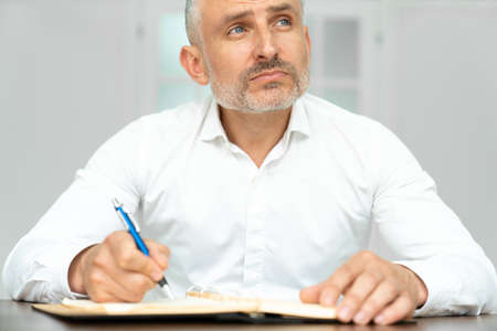 From below of excited charismatic ethnic guy in white shirt with pen in hand creating project at workplace