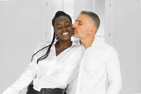 Front view of businessman kissing sexy colleague in office, waist up shot Standard-Bild - 153361268