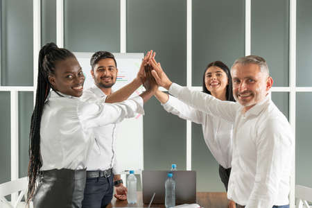 Teamwork concept. Happy successful multiracial business team giving a high fives gesture as they laugh and cheer their success Standard-Bild - 153361271