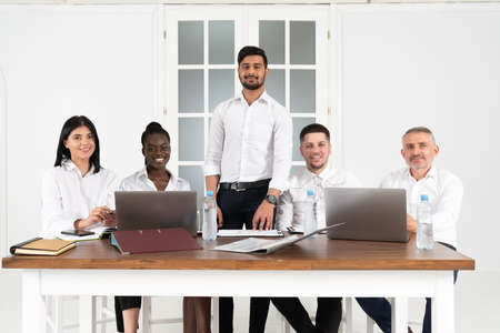 Group of designers smiling while working around an office table