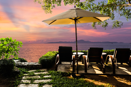The chairs are set in a tree garden and the grass on the beach at sunset is relaxing.