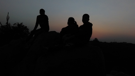 Three friends silhouette at evening at peace