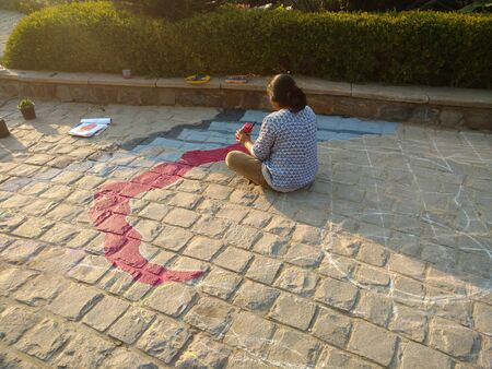 Female Painter painting on ground