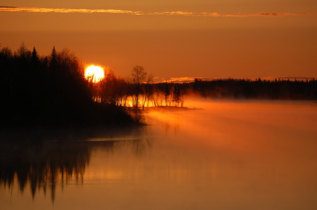 A colorful sunrise over a foggy Northern River Stock Photo