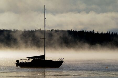 Silhouette of a sailboat in the morning mist