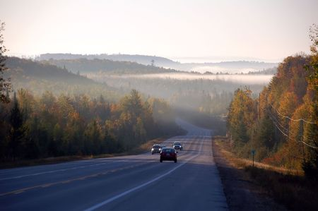 A beautiful autumns landscape showing a road in the morning with fog and mist photo