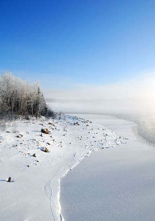 Winter landscape showing a frozen river on a very cold day photo