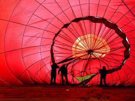 View of the inside of a red hot air balloon being infalated Stock Photo
