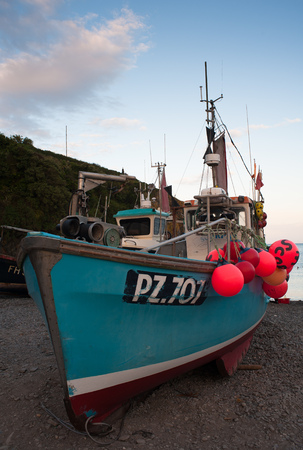 A blue fishing boat with bright orange floats sits on the beach at Cadgwith on a summer evening.