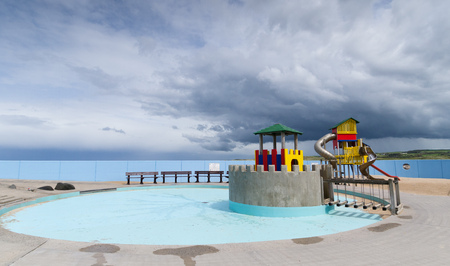 A chidrens playground and padding pool with a stormy sky in the background.