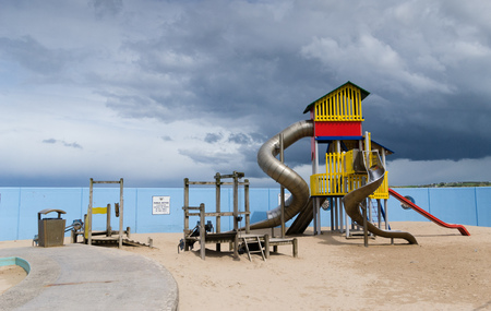 A chidrens playground with a stormy sky in the background. Stock Photo