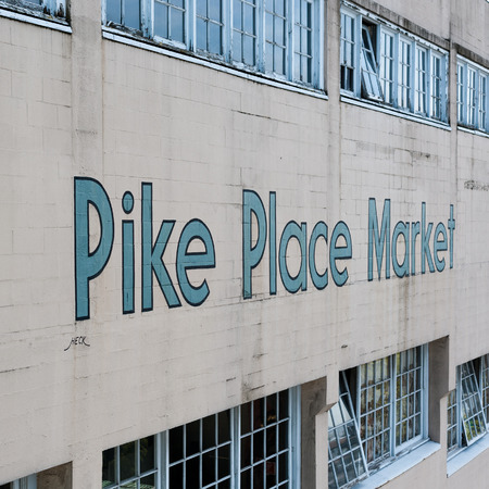 A painted sign for Pike Place Market, Seattle, Washington, blue against a white brick wall.
